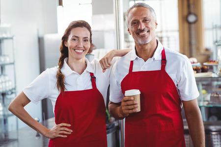 delantal: Dos baristas sonriendo a la c�mara en el caf� Foto de archivo