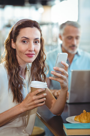 bakery store: Pretty brunette looking at camera with smartphone and coffee in her hands in the bakery store
