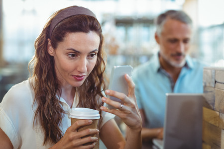 bakery store: Pretty brunette using her smartphone with coffee in her hand in the bakery store Stock Photo