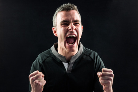 people shadow: Excited rugby player yelling out on a black background Stock Photo