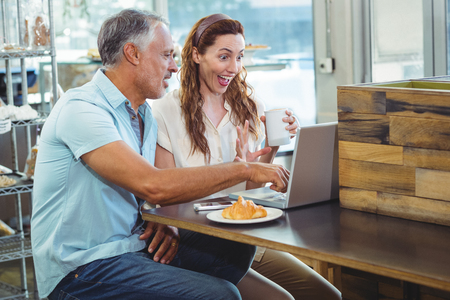 bakery store: Happy couple watching something funny on laptop in the bakery store Stock Photo