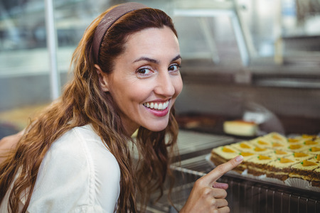 bakery store: Pretty brunette pointing at pastries through the glass in the bakery store