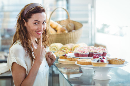 hesitating: Dudando mujer bonita mirando a la c�mara en la tienda de la panader�a