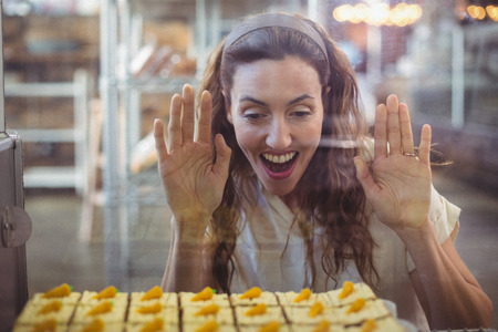 bakery store: Pretty brunette looking at pastries through the glass in the bakery store