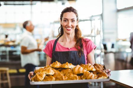 Baker met lade van verse croissant in de keuken van de bakkerij