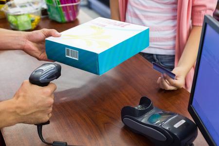 codigo de barras: Mujer sonriente en la caja registradora pagando con tarjeta de crédito y escanear un producto en el supermercado Foto de archivo