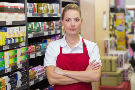 Portrait of serious blonde worker with arms crossed in supermarket Stock Photo