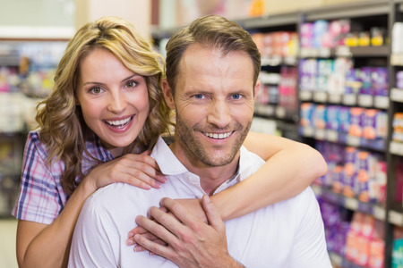 arm around: Portrait of smiling casual couple with arm around in supermarket