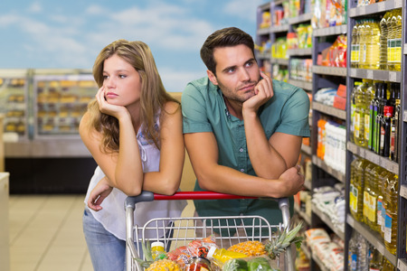 woman shopping cart: Serious bright couple buying food products at supermarket