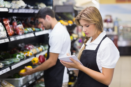 grocery shelves: Serious staff woman wrting on notepad at supermarket Stock Photo