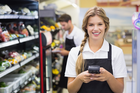 Portrait of smiling pretty blonde woman using handheld at supermarket Stock Photo