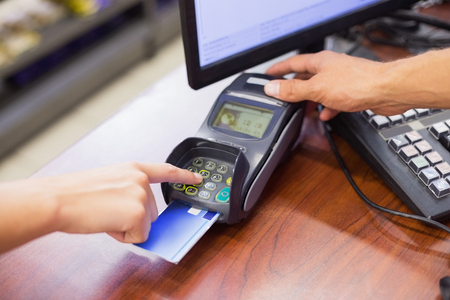 pin code: Woman paying with her credit card and doing his pin code in supermarket
