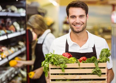 supermercado: Retrato de un hombre sonriente personal que sostiene una caja de verduras frescas en el supermercado