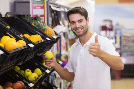 Portrait of a smiling handsome man buying a fruit with thumb up at supermarket