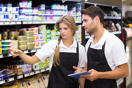 grocery shelves: Serious colleagues showing and using a digital tablet at supermarket