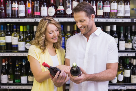 ar: Smiling casual couple looking ar wine bottle in supermarket