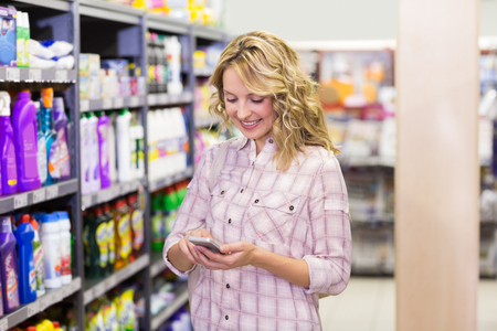 retail shopping: Smiling pretty blonde woman using her smartphone in supermarket