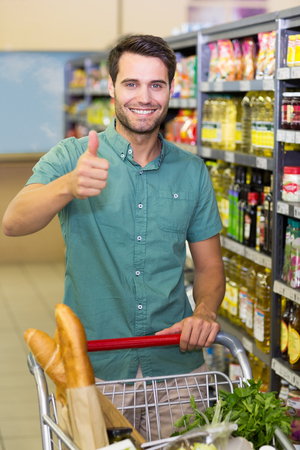 thumbs: Portrait of smiling man buy products with his trolley and thumb up at supermarket