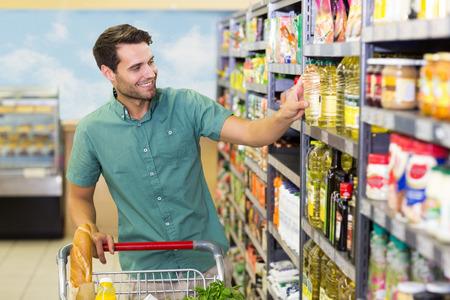 carro supermercado: Hombre sonriente que toma un aceite en el pasillo en el supermercado