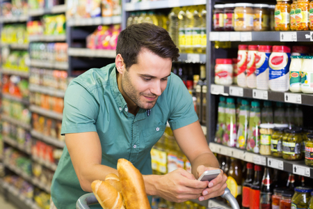 typing man: Smiling man buy food and using his smartphone at supermarket Stock Photo
