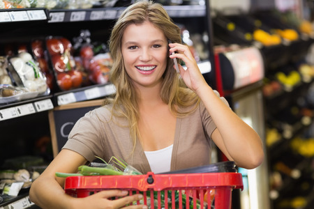 phoning: Portrait of smiling blonde woman buying vegetables and phoning at supermarket Stock Photo
