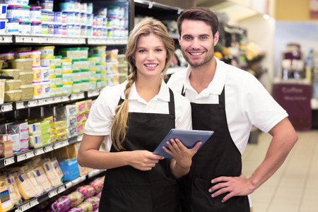 Portrait of smiling colleagues using a digital tablet at supermarket