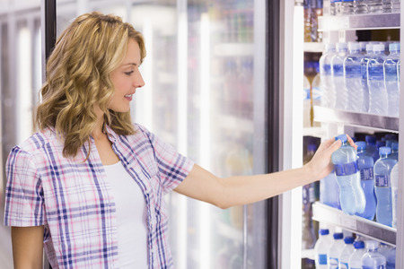 fridge: Smiling pretty blonde woman taking a water bottle in supermarket Stock Photo