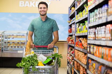 supermercado: Retrato de hombre sonriente caminando con su mesa con pasillo en el supermercado