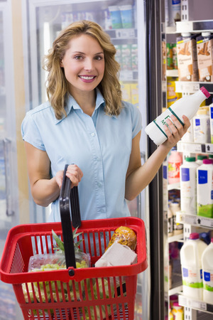 milk bottle: Portrait of smiling woman having on her hands a fresh milk bottle and shopping basket in supermarket Stock Photo