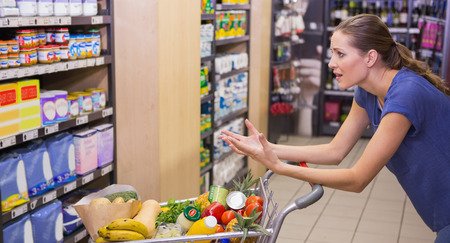 sorprendido: Mujer sorprendida que mira el producto en el estante en el supermercado