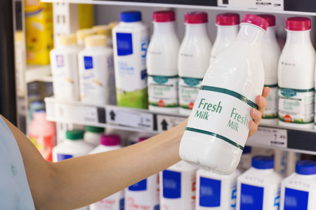 그녀의 손에 슈퍼마켓에서 신선한 우유 병을 가진 여자 스톡 콘텐츠