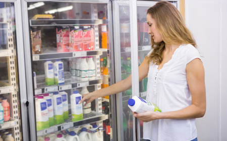 milk bottle: Pretty woman taking bottle of milk at supermarket