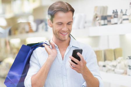 centro comercial: Un hombre sonriente feliz mirando el teléfono en el centro comercial