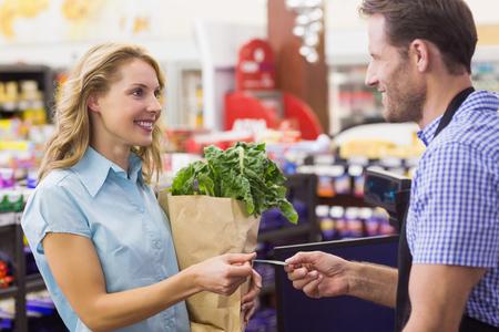 maquina registradora: Mujer en la caja registradora pagando con tarjeta de crédito en el supermercado