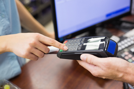 maquina registradora: Woman at cash register paying with credit card in supermarket