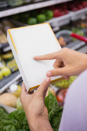shopping list: Over shoulder view of woman pointing her shopping list