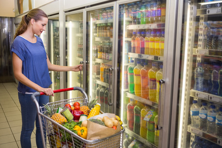 pretty: Pretty woman looking at camera and taking product on Pretty woman taking botlte of water in freezer  at supermarket Stock Photo