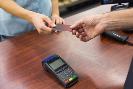 register: Woman at cash register paying with credit card in supermarket