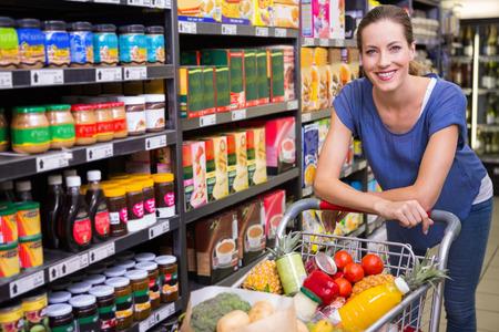 empujando: Mujer bonita que mira la cámara y que empuja la carretilla en el supermercado