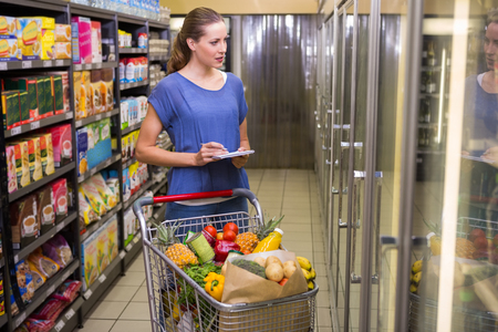 retail shopping: Pretty woman looking at product on freezer at supermarket Stock Photo