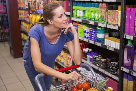 empujando: Pensativo morena guapa empuja la carretilla en el supermercado