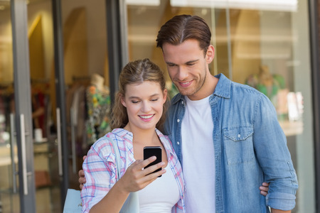 light hair: Happy couple looking at smartphone at the mall