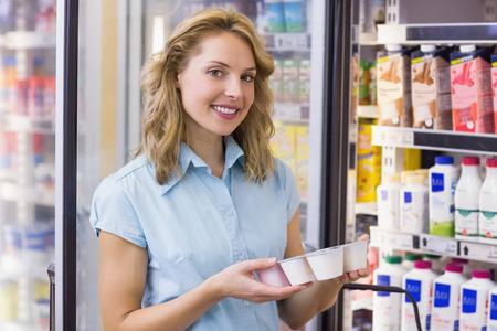 yogur: Retrato de una mujer sonriente que tiene en sus manos un yogur fresco en supermercado