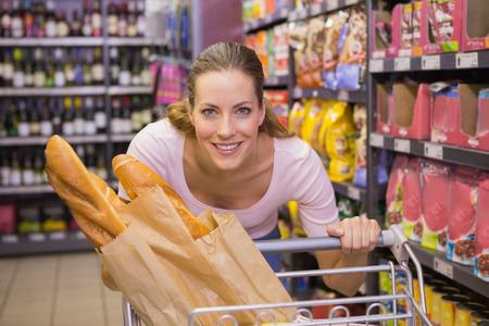 empujando: Mujer bonita feliz empujando carrito de supermercado
