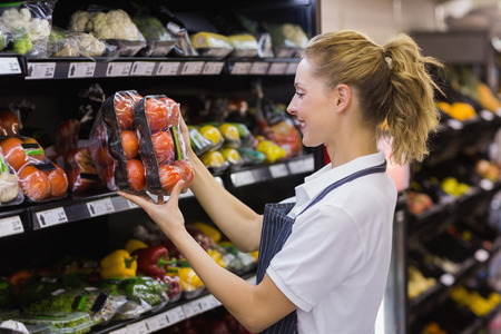grocery shelves: Side view of a smiling blonde worker taking a tomatoes in supermarket