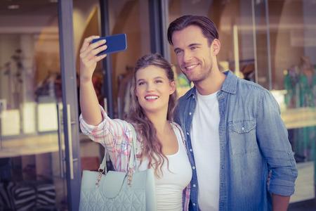sonriente: Una pareja feliz sonriendo tomando selfies en el centro comercial
