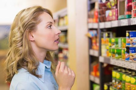 supermercado: Mujer rubia bonita que mira en los estantes en supermercado