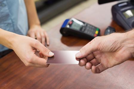 pagando: Mujer en la caja registradora pagando con tarjeta de crédito en el supermercado