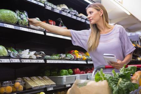 abarrotes: Sonriente mujer de la lectura en su bloc de notas en el pasillo en el supermercado