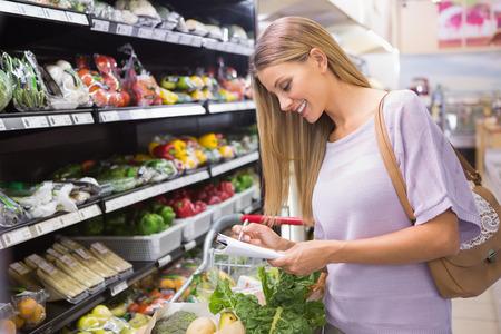 tienda de ropa: Sonriente mujer de la lectura en su bloc de notas en el pasillo en el supermercado